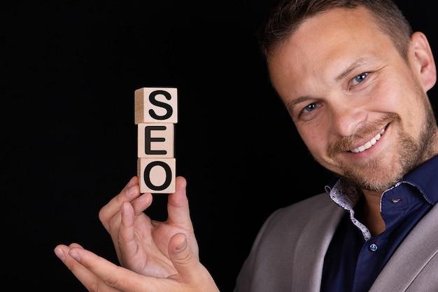 ビジネスマンは彼の手にseoという言葉で立方体、ブロックを持っています。ビジネスコンセプト。