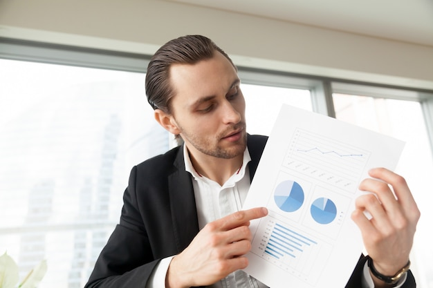 Businessman holds document with infographics