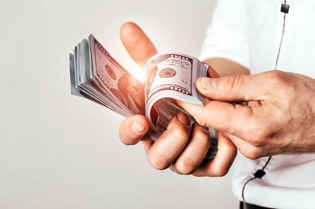 Бизнесмен держит доллары в руках. богатый человек считает деньги в комнате.