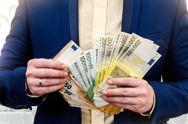 The businessman holds the euro in hands