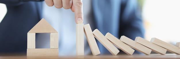 Бизнесмен держит падающие фигурки деревянных блоков на доме