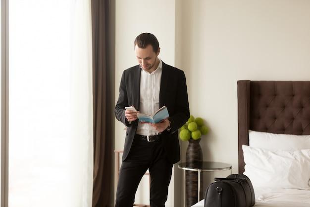 L'uomo d'affari tiene la brochure della guida