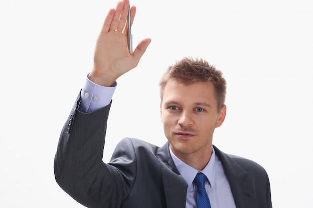 A businessman holds a hand up with a pen