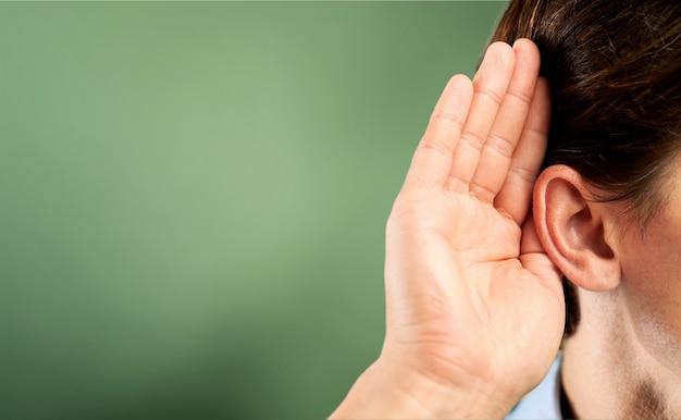 ビジネスマンは彼の耳の近くで彼の手を握り、何かを聞いています