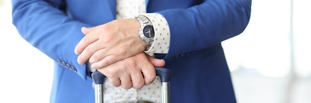ビジネスマンはスーツケースのハンドルに手を握ります