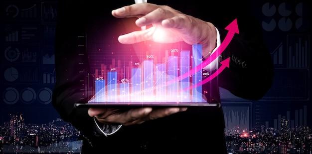 Бизнесмен держит голограмму бизнес-аналитики и финансов