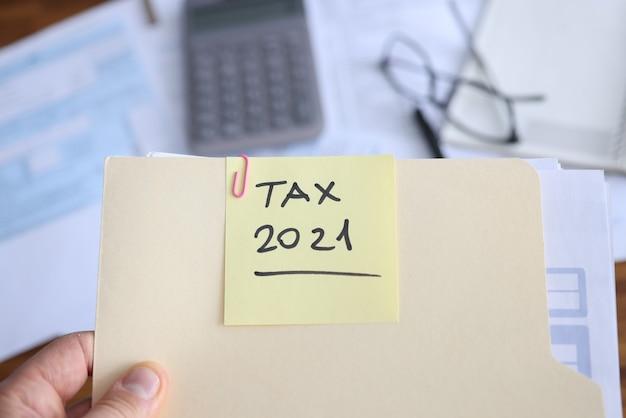 Бизнесмен держит в руках папку с документами для подачи налоговой декларации