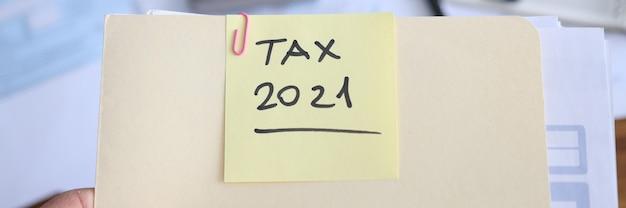 ビジネスマンは、納税申告書を提出するための書類を手に持っています