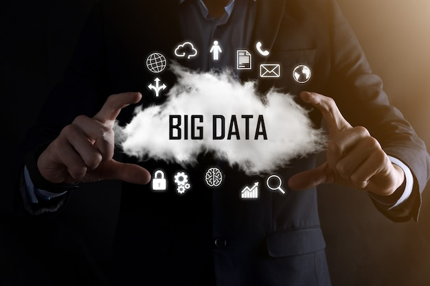 Businessman holds the inscription word big data. padlock , brain ,man, planet,graph, magnifier, gears, cloud, grid, document, letter, phone icon.