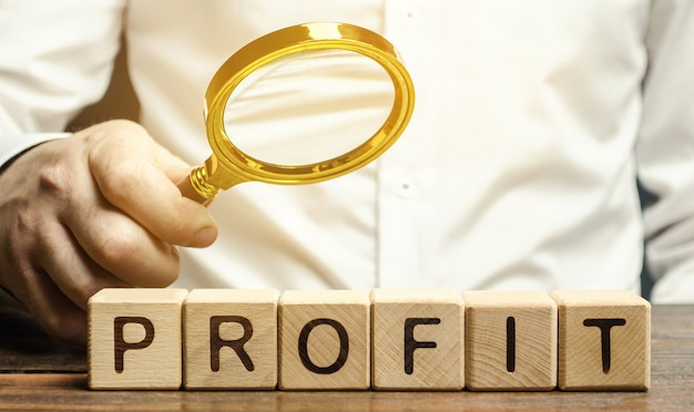 Businessman holds a magnifying glass over the word profit.