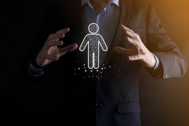 Businessman holds man person icon on dark tone background.