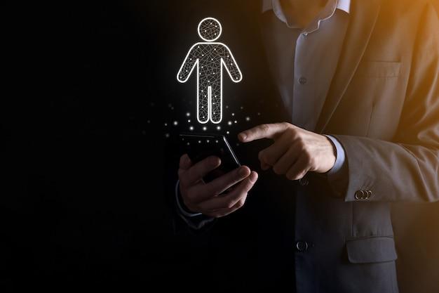 ビジネスマンは暗いトーンの背景に人の人のアイコンを保持します。hr人、人のアイコン採用、雇用、チームビルディングの技術プロセスシステムビジネス。組織構造の概念。