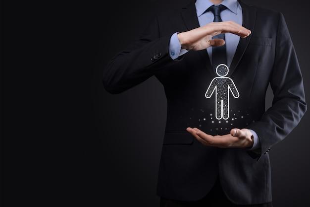 ビジネスマンは暗いトーンの背景に人の人のアイコンを保持します。hr人、人のアイコン採用、雇用、チームビルディングと技術プロセスシステムビジネス。組織構造の概念。
