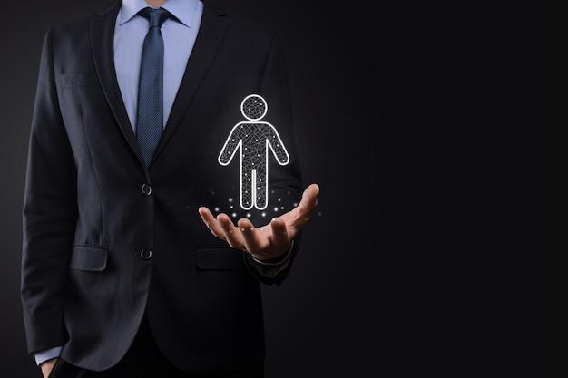 ビジネスマンは暗いトーンの背景に人の人のアイコンを保持します