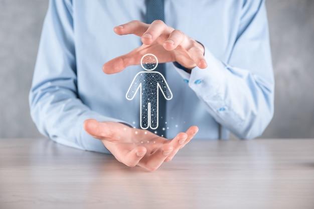 ビジネスマンは暗いトーンの表面に人の人のアイコンを保持します。