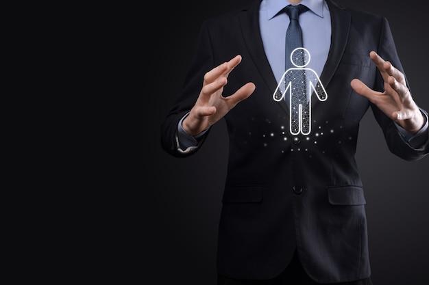 Бизнесмен держит значок человека человека на темной поверхности тона