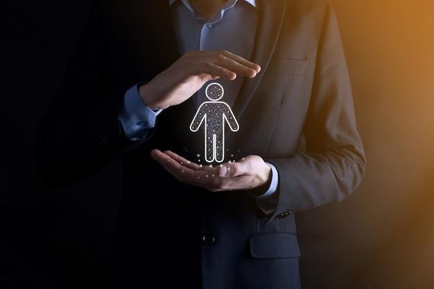 ビジネスマンは暗いトーンの表面に人の人のアイコンを保持します