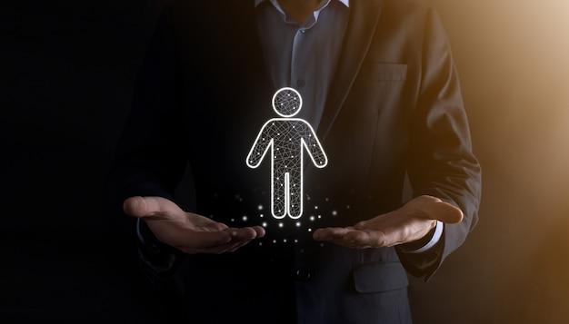ビジネスマンは暗いトーンの壁に人の人のアイコンを保持します。hr人、人のアイコン採用、雇用、チームビルディングを伴う技術プロセスシステムビジネス。