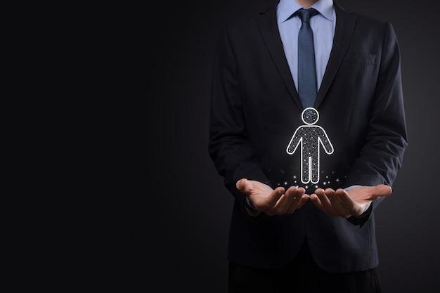 ビジネスマンは暗いトーンの背景に人の人のシンボルを保持します。hr人、人のアイコン採用、雇用、チームビルディングを伴う技術プロセスシステムビジネス。組織構造の概念。