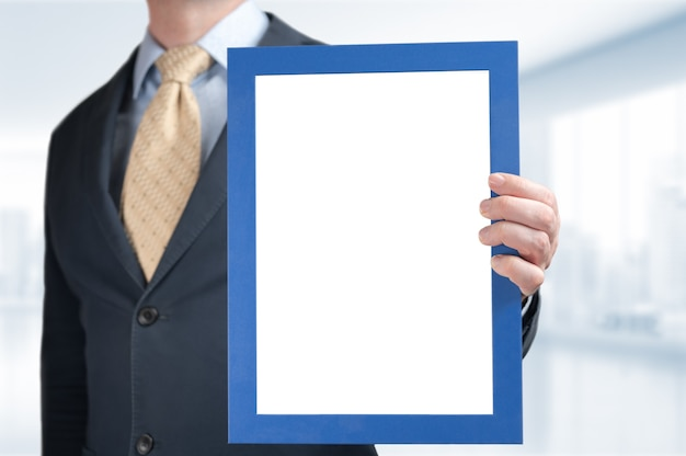 Businessman holds mockup frame with blank white space for certificate, diploma, painting. mockup businessman holding picture certificate graduation diploma frame on blurred office background.