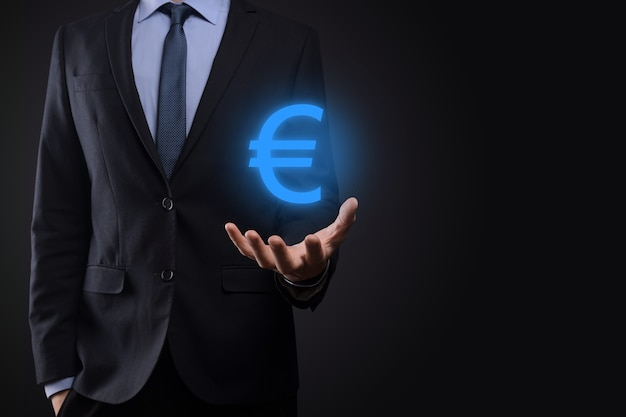 Businessman holds money coin icons eur or euro on dark tone background..growing money concept for business investment and finance.