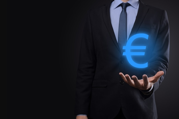 Businessman holds money coin icons eur or euro on dark tone background.