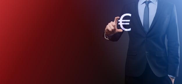 ビジネスマンは暗いトーンの背景にお金のコインアイコンeurまたはユーロを保持しています。ビジネス投資と金融のためのお金の概念を成長させます。