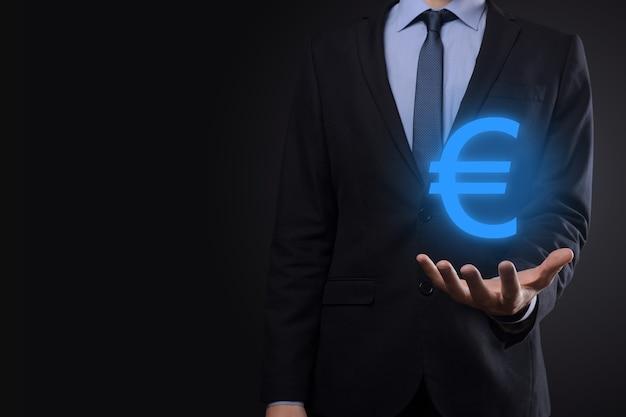 ビジネスマンは暗いトーンの背景にお金のコインアイコンeurまたはユーロを保持しています。