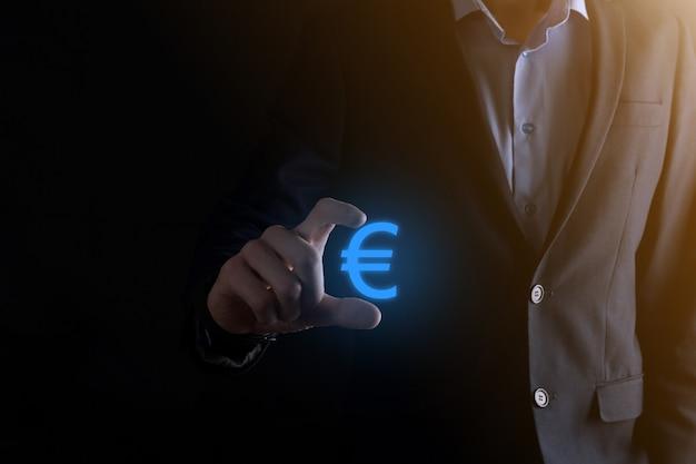 Бизнесмен держит значки монет денег (евро или евро) на темной поверхности тона