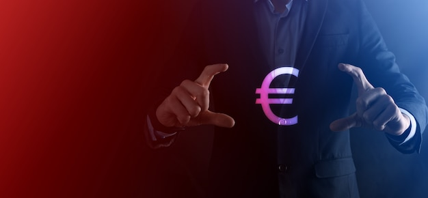 ビジネスマンは暗いトーンの表面にお金のコインアイコンeurまたはユーロを保持します