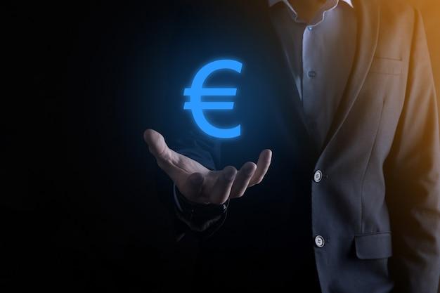 ビジネスマンは暗いトーンの壁にお金のコインアイコンeurまたはユーロを保持しています。ビジネス投資と金融のためのお金の概念を成長させます。