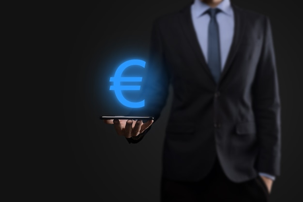 ビジネスマンは暗いトーンの壁にお金のコインのシンボルeurまたはユーロを保持しています。ビジネス投資と金融のためのお金の概念を成長させます。
