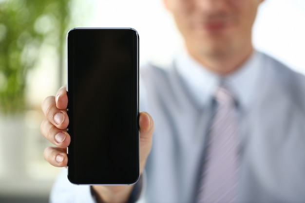 A businessman holds a new smartphone