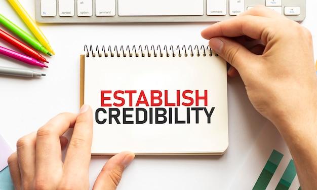 ビジネスマンは、テキストでメモ帳を保持しますestablish credibility