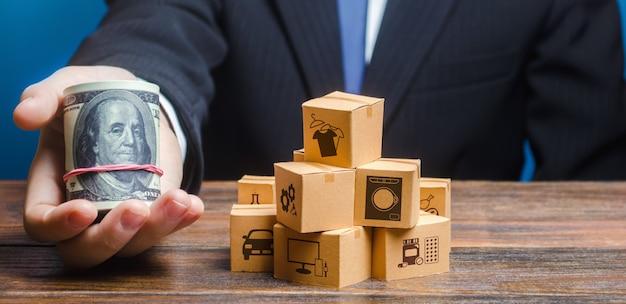 ビジネスマンは箱の山の近くでドルの束を差し出します。