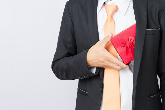 Businessman holds out the gift red box, isolated background