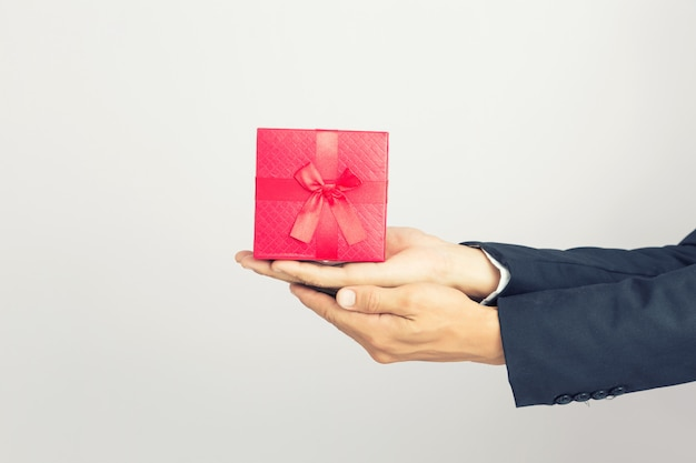 Businessman holds out the gift red box