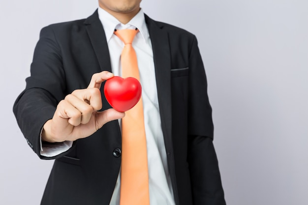 Businessman holds out the  red heart, isolated background