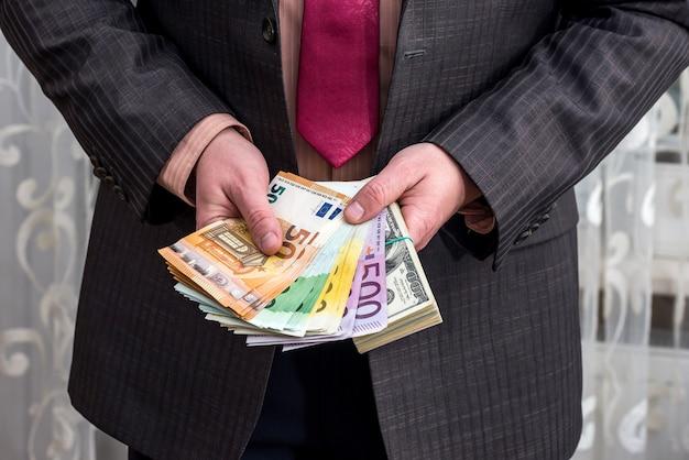 ビジネスマンは彼の手にドルとユーロのパックを持っています