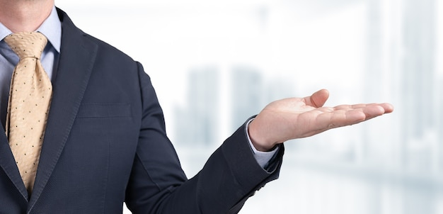Businessman holds palm with blank space for your text and design on blurred office background