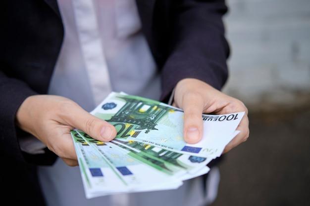 Бизнесмен держит бумажные деньги, валюту из евро