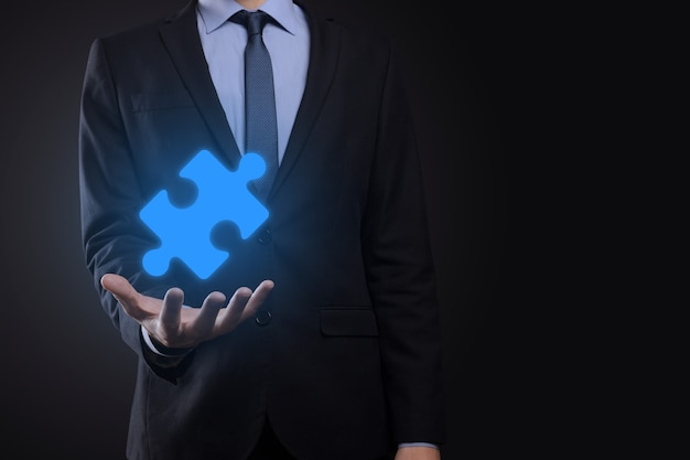 Businessman holds a piece of puzzle jigsaw in his hands.the concept of cooperation, teamwork, help and support in business.