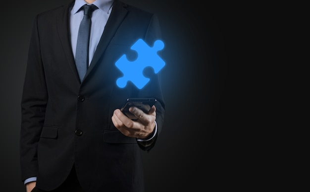 Businessman holds a piece of puzzle jigsaw in his hands