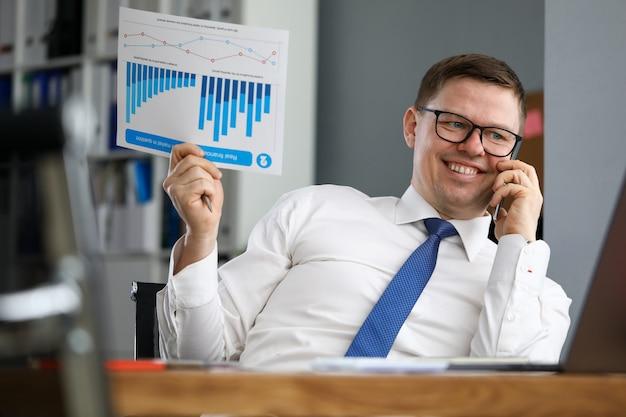 ビジネスマンはレポートを保持し、電話で話す