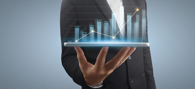 Businessman holds a tablet with growing graph hologram on grey background