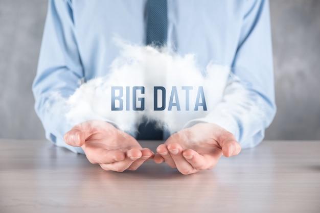 Бизнесмен держит надпись большие данные. замок, мозг, человек, планета, график, лупа, шестерни, облако, сетка, документ, письмо, значок телефона.