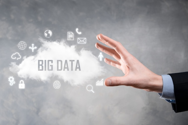 ビジネスマンは、碑文、単語ビッグデータを保持しています。南京錠、脳、人、惑星、グラフ、拡大鏡、歯車、雲、グリッド、ドキュメント、手紙、電話のアイコン。