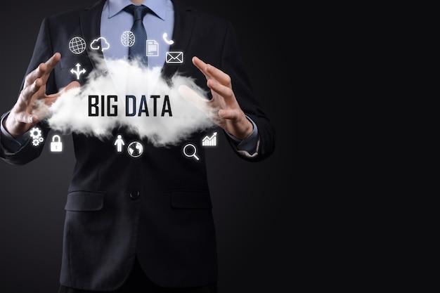 Бизнесмен держит слово надписи большие данные. замок, мозг, человек, планета, график, лупа, шестерни, облако, сетка, документ, письмо, значок телефона.