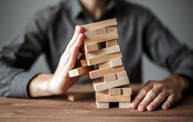 Бизнесмен держит модель бизнеса, сделанную из деревянных блоков