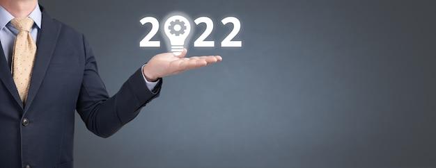 ビジネスマンは彼の手に革新のシンボルで2022年を保持します。 2022年の新年とコピースペースのある灰色の青い背景の上の電球。バナー